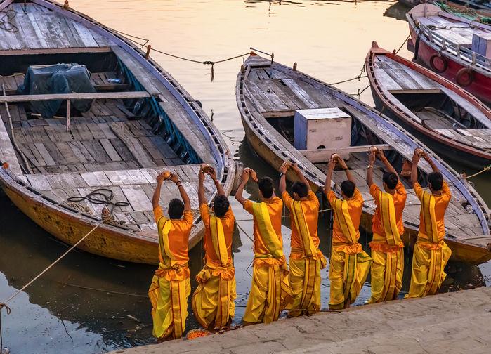 Präster i saffransgult ber vid Ganges